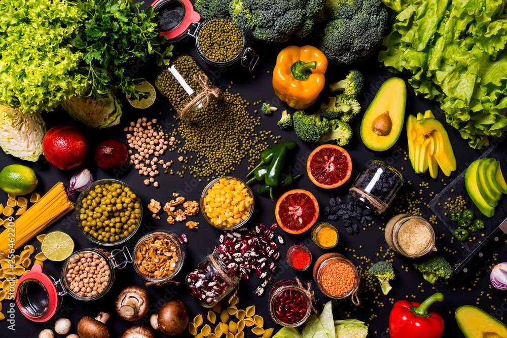 Big set of fresh vegetables and fruits on black background. Different colorful fresh vegan food. Flat lay.