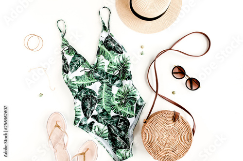 Obraz Woman's beach accessories: swimsuit with tropical print, rattan bag, straw hat on white background. Summer background. Flat lay, top view. - fototapety do salonu