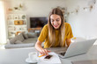 Leinwanddruck Bild - Young woman using her laptop at home
