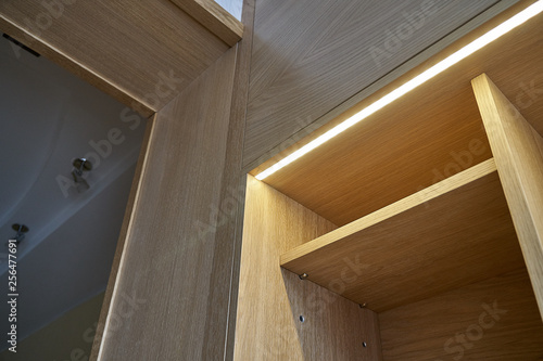 Wooden cupboard with drawers, empty shelves and LED lights Wallpaper Mural