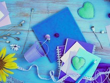 Seasonal Summer Composition Of A Pair Of Felt Hearts, Paper With A Pencil, Notebooks And Decor On A Blue Table, Top View, Concept Of Writing A Plan For Preparing For A Romantic Trip, Relaxation, Vint
