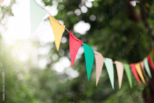 Fotografia  Garland of colorful flags at sunset in summer garden