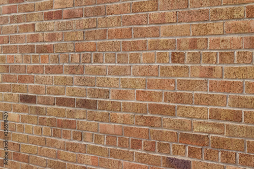 Vintage red brown multi-colored textured brick wall background in American bond brickwork pattern with shades of tan, salmon and pink (angle view)