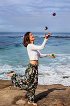 Woman Juggling By The Ocean