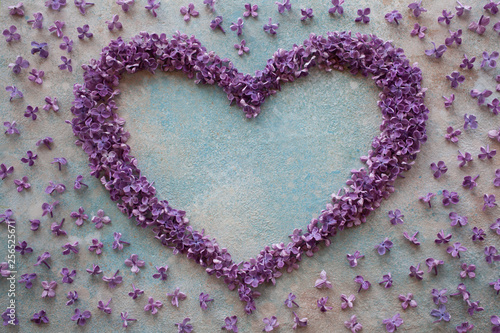 Valokuva  Decorative plaster background with a heart of lilac flowers