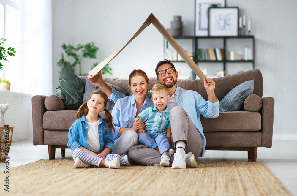 Fototapeta concept of housing and relocation. happy family mother father and kids with roof at home .