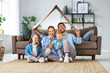 canvas print picture - concept of housing and relocation. happy family mother father and kids with roof at home .
