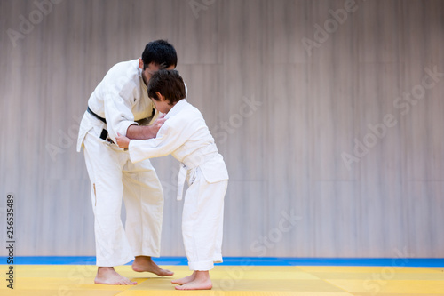Photo  Trainer and young judoka are engaged in judo class in a dojo