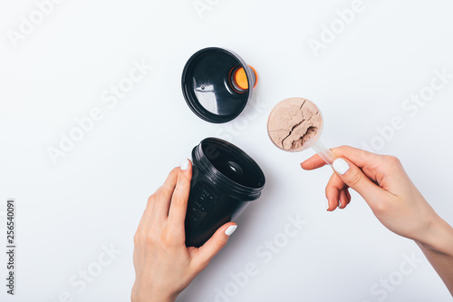 Fototapeta  Woman's hands putting scoop of chocolate protein