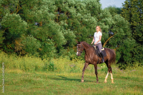 Poster Equitation Young blond woman with long hair jockey rider jumping on a bay horse on a background of field and forest