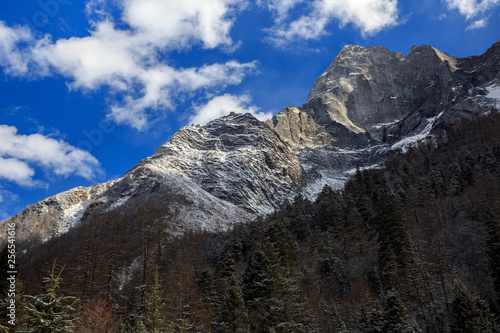 ShuangQiao Valley Scenic Area, Siguniangshan - Four Girls Mountain National Park in Sichuan Province, China. Snow Capped Jagged Mountains with clouds forming at the summit. Blue Sky, Snow Mountains