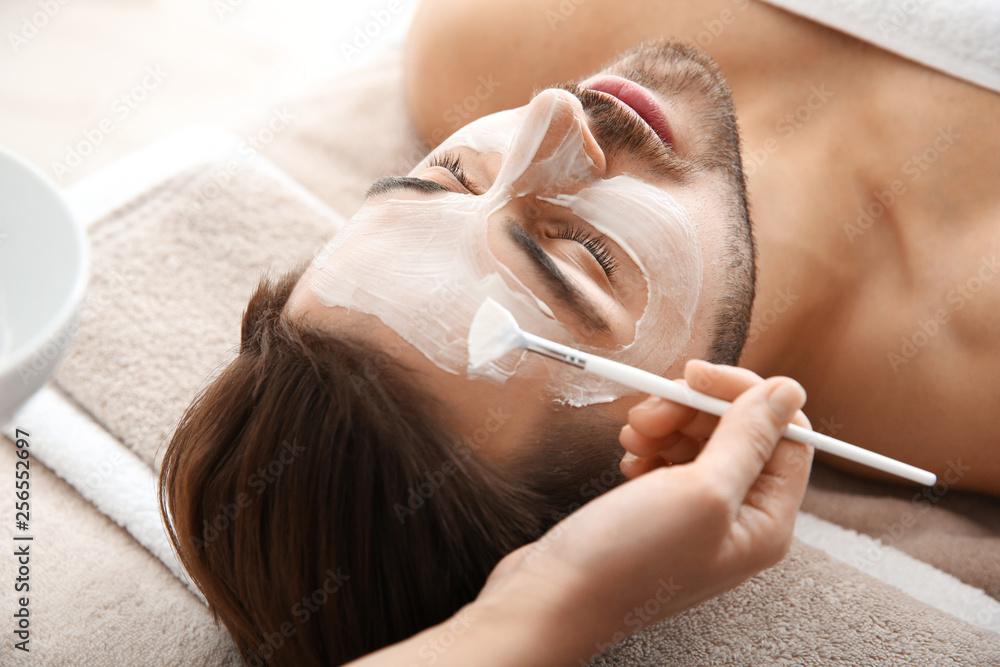 Fototapeta Cosmetologist applying mask on client's face in spa salon