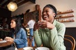 Leinwanddruck Bild - Young woman laughing over coffee with friends in a cafe