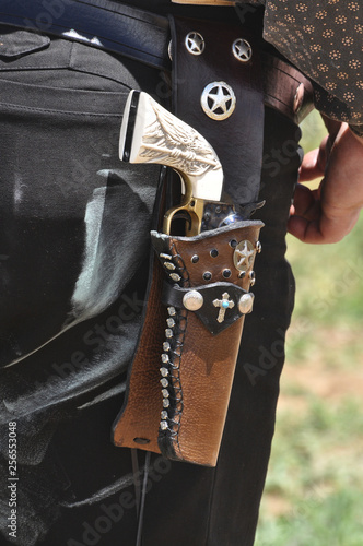 Western pistol gun with ivory handle grip in leather holster worn by