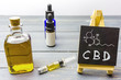 canvas print picture - Cbd oil in glass bottle and chalkboard with molecule drawing on table