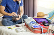 Young man hurring up to meeting and talking by phone and taking notes packing for Preparation travel suitcase at home
