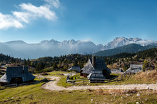 Wooden Houses At Velika Planina With Alps In The Backround