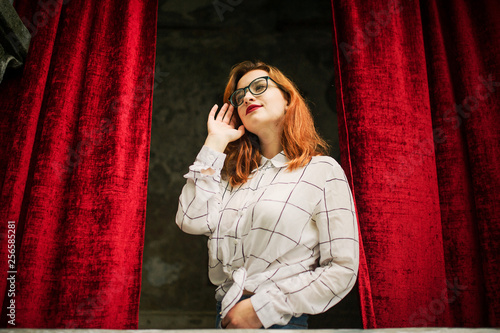 Fotografía  Attractive redhaired woman in eyeglasses, wear on white blouse posing at arch of open red curtains