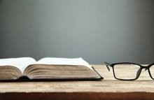 Open Book And Glasses On The Wooden Table.