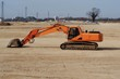 Excavator in a flat plain outside an area of ​​industrial development. Side view