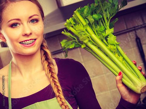Fotografia  Woman in kitchen holds green celery