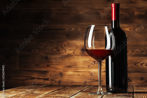 Glass and bottle with delicious red wine on table against wooden background