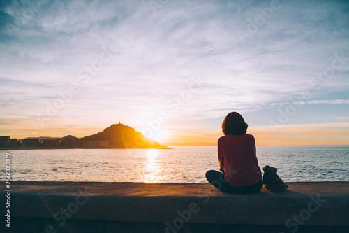 Fototapeta premium Młoda kobieta oglądając zachód słońca nad morzem w San Sebastian