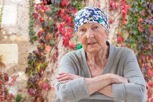 Fototapeta Portrait of mature woman recovering after chemotherapy and looking at camera whi