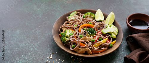Photo  Stir fry noodles with chicken meat and vegetables in bowl on dark green backgrou