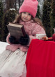 Girl child in pink coat at winter forest