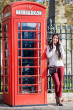 Young, Attractive London Tourist Girl Stands Next To A Red Telephone Booth During Her Sightseeing Trip