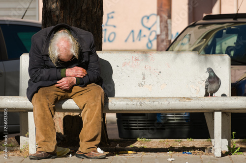 homeless man sitting on a bench in the park Fototapeta