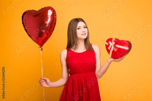Photo  happy blonde in red dress holding a balloon and a gift box