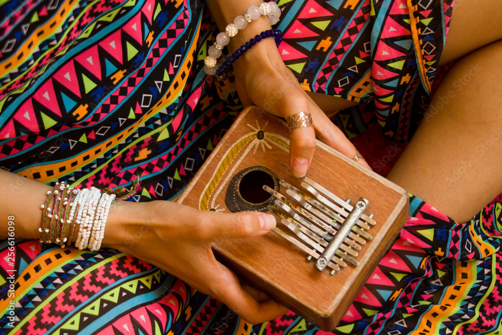 Fototapeta Woman holding kalimba in her hands and playing