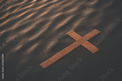 Fotografia Wooden cross floating on water surface at dawn