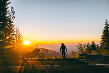 Silhouette Of Man Biker And Adventure Motorcycle On The Road With Sunset Light Background. Top Of Mountains, Tourism Motorbike, Vacation Active Lifestyle. Transfagarasan, Romania.