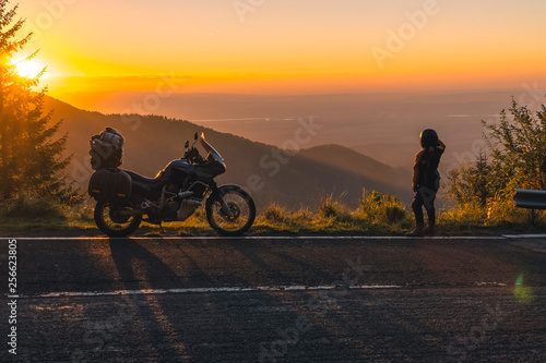 girl in full motorcycle equipment, stands on the side of the road over a cliff and looks into the distance at beautiful sunset in the mountains. Adventure motorcycle, Transfagarasan, Romania