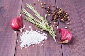 Goździki czosnek, rozmaryn, sól morska i pieprz na drewnianym tle