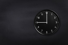 Black Wall Clock Showing Nine O'clock On Black Chalkboard Background. Office Clock Showing 9am Or 9pm On Black Texture