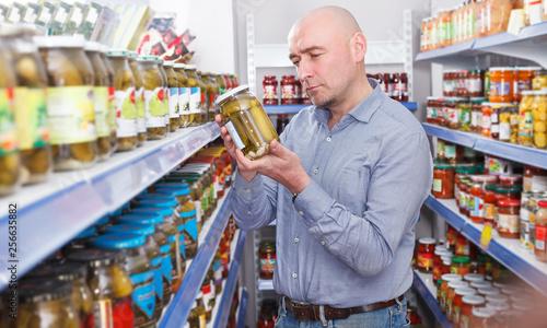 Fotografía  Man customer choosing pickle goods in food store
