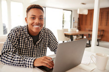 Black Male Teenager Using A Laptop Computer At Home Smiling To Camera, Close Up