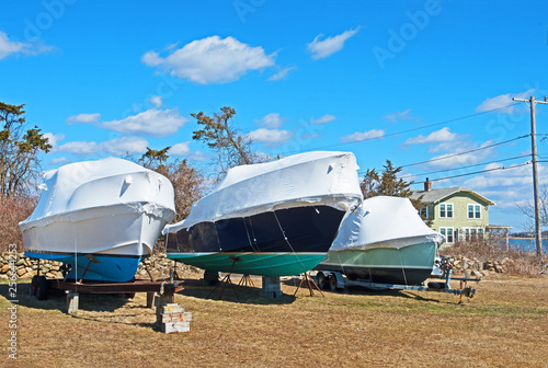 Three boats are stored for the winter in Fairhaven, Massachusetts, out of the water and on blocks with shrinkwrap style covers to protect them from the elements Canvas-taulu