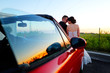 Beautiful wedding couple watching the sunset in a convertible car.