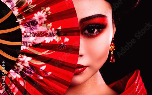 Tablou Canvas beautiful Japanese girl in kimono with a fan on a black background