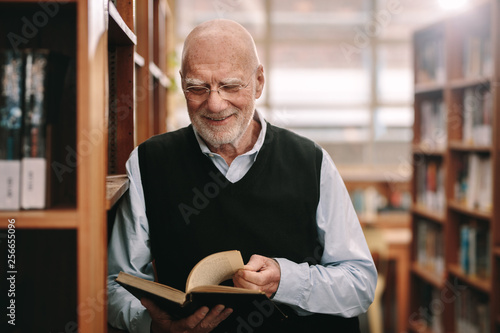 Smiling senior man looking at a book standing in a library