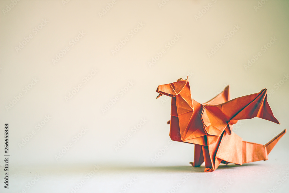 Fototapeta Origami dragon in red on a plain background.  Paper Origami. Сopy space