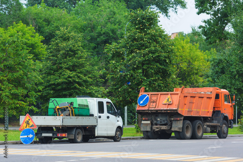 Poster Pixel Road signs the road is being repaired. KAMAZ orange against the trees. Cars for road repairs.