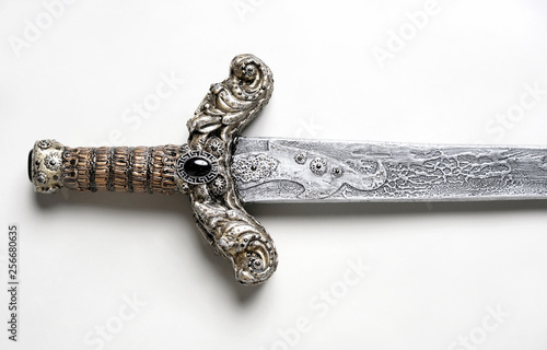 Foto Closeup of vintage metal sword decorated with gems on white background