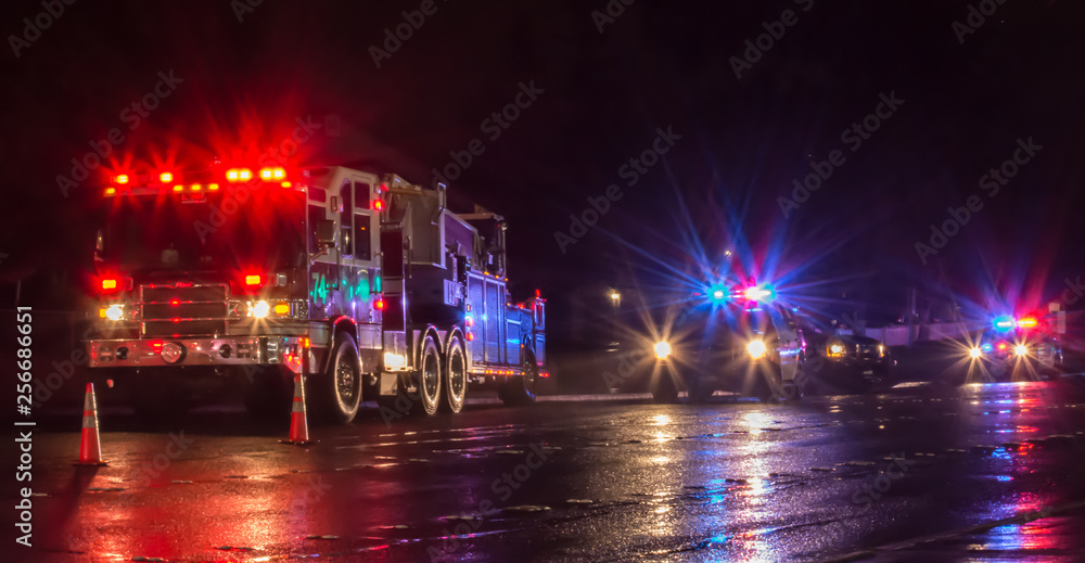 Fototapeta First Responders - firefighters and police officers - on a wet night