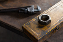 Giant Industrial Steel Nut Laying On A Yellow Toolbox On Top Of A Work Bench - Heavy Duty Threaded Nut Next To An Adjustable Hand Tool Pipe Wrench